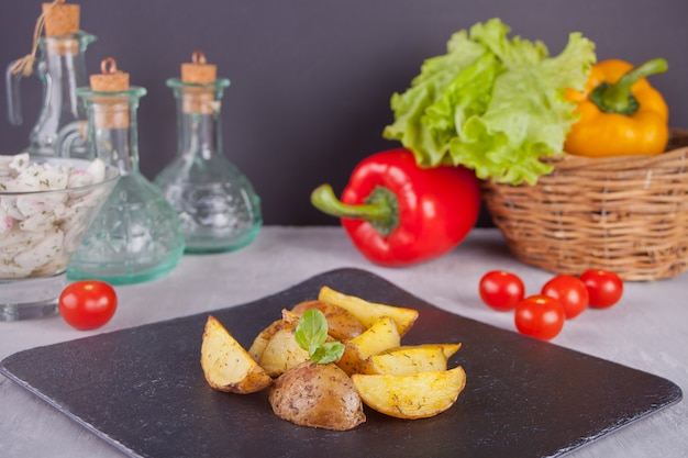 Homemade baked potato wedges with herbs on a black plate with vegetables on the background
