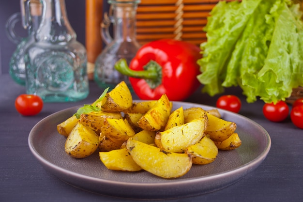 Homemade baked potato wedges with herbs on gray plate with vegetables on the background.