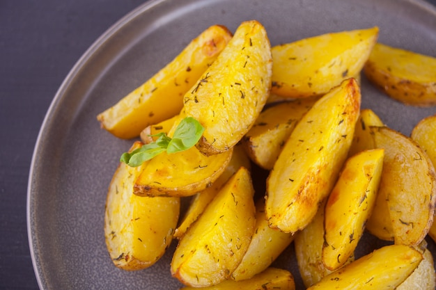 Homemade baked potato wedges with herbs on gray plate.