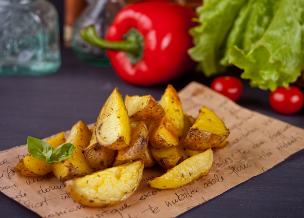 Homemade baked potato wedges with herbs with vegetables on the background.