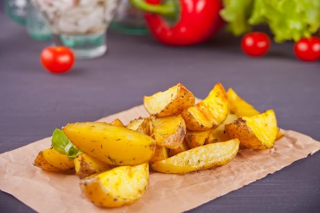 Домашние запеченные картофельные дольки с зеленью с овощами на поверхности.