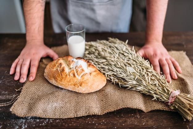 自家製ベーカリーコンセプト、自然の有機食品。焼きたてのパンのパンに対してシャキッとした皮、小麦の束、黄麻布の上に牛乳のガラスに対してパン屋の手。