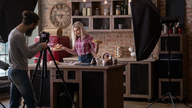 수제 빵집. 요리 블로그. 백 스테이지 사진. 파이와 젊은 여자를 촬영하는 카메라를 가진 남자입니다.