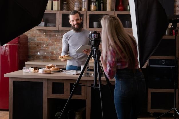 수제 빵집. 요리 블로그. 백 스테이지 사진. 카메라 촬영 웃는 젊은 남자 태블릿 및 신선한 파이와 여자.