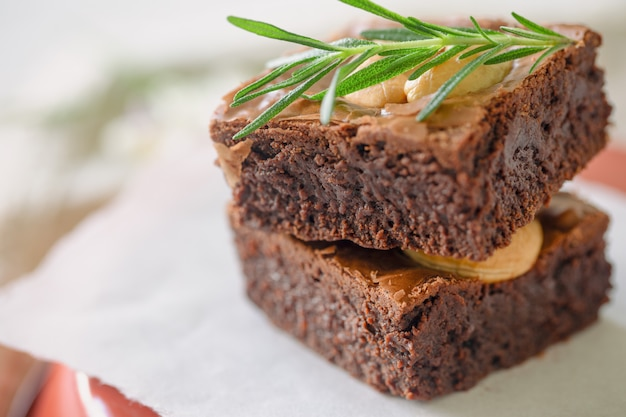 Homemade bakery dark chocolate fudge brownies cake topping with cashew nut and rosemary stacked on white paper with copy space. delicious bitter sweet and chewy. brownie is one type of chocolate cake.
