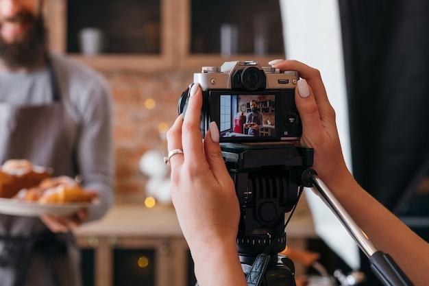 수제 베이킹. 요리 취미. 백 스테이지 사진. 신선한 케이크와 파이와 앞치마에 여자 촬영 남자.