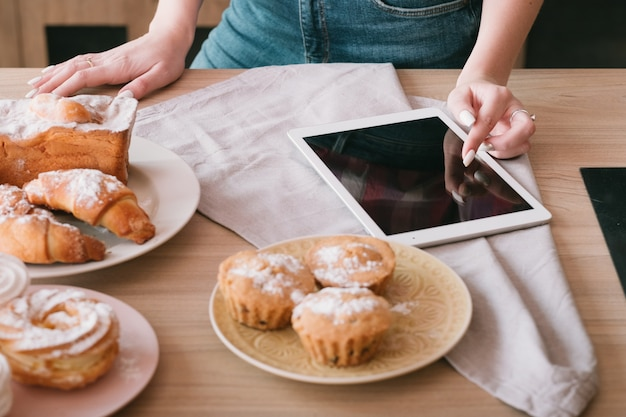 수제 베이킹. 여성 요리 취미. 여자 검색 태블릿입니다. 테이블에 신선한 파이 구색입니다.