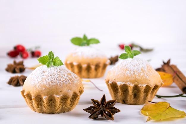 秋のスタイルで自家製のベーキング。シナモンスティック、アニススター、カボチャ、ローズヒップの果実と木の板でおいしいカップケーキ。白いテーブルの上。