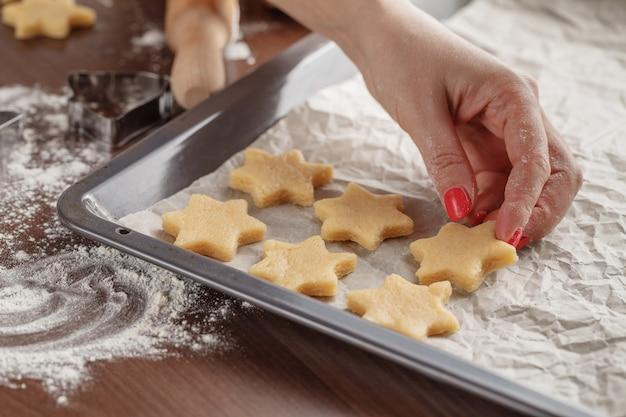 Домодельная выпечка, сцена кухни показывая женщину держа поднос выпечки с отрезанными печеньями shortbread на бумаге выпечки готовой быть сваренным.