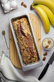 Домашний банановый миндальный хлеб с орехами пекан и ингредиентами в форме для выпечки на деревянной доске