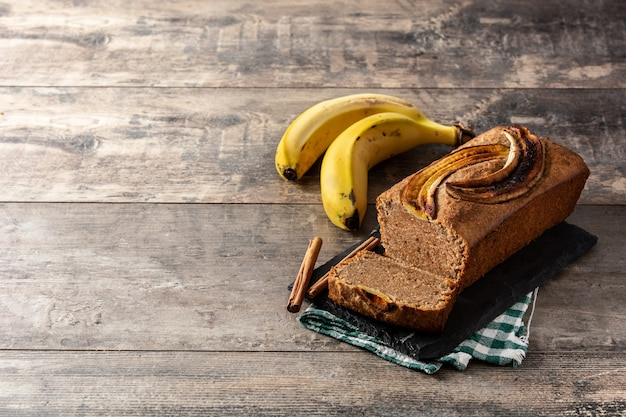 Homemade banana bread on rustic wooden table.