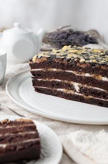 수제 바나나 케이크. 비스킷 초콜릿 케이크. 버터 크림에 담근다. 초콜릿으로 장식. 하얀 접시에. 배경에는 이전 주전자와 머그잔이 있습니다.