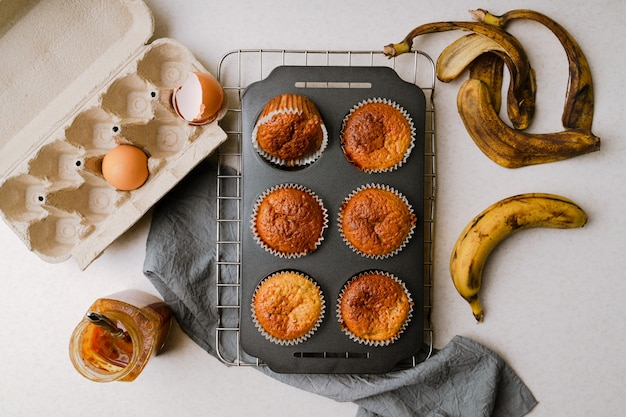 Homemade banana and honey muffins in mufin tray cooling on rack, eggs, banana peel, honey on kitchen tabletop