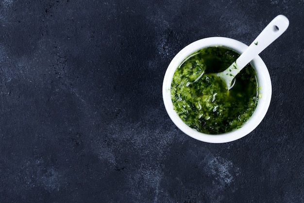 Homemade basil pesto with parsley in bowl.