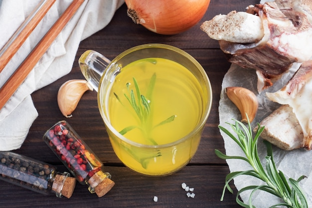 Домашний бульон из говяжьей кости и овощей с приправой из куркумы в стакане
