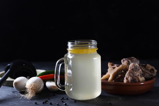 黒いスペースにガラスの貯蔵瓶に自家製の牛骨スープ