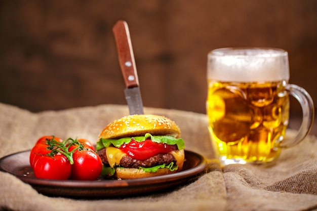 Homemade beef burger and fresh vegetables on clay dish with glas