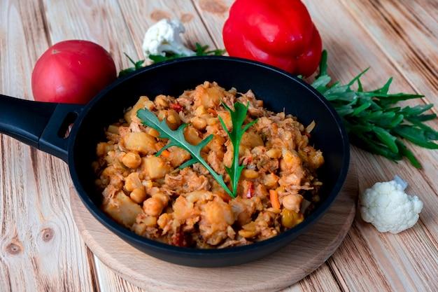 Домашнее тушеное мясо из говядины с красным вином, овощами, картофелем, луком, морковью, цветной капустой, перцем с томатным соусом, чесноком и зеленью в жаровне на деревянном столе. деревенская еда на деревянных фоне