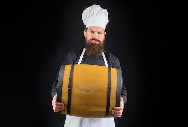自家製ビールの木製の樽のひげを生やした料理人と熟成のためのビール醸造所の木製の樽