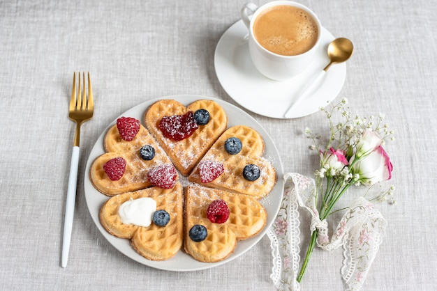 Homemade belgian heart waffles with strawberry sauce and berries with flowers