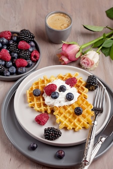 Homemade belgian waffles, gray ceramic cup of coffee and berries