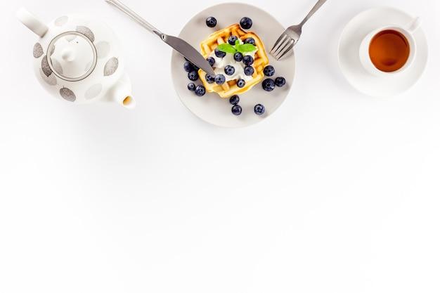 Домашние бельгийские вафли на сервированном столе на белом
