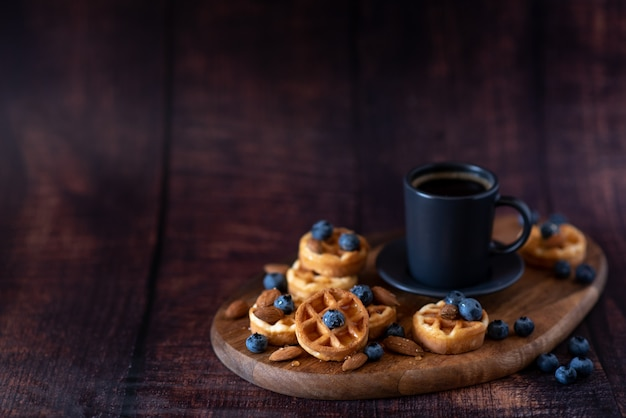 Homemade belgian waffles, white ceramic cup of coffee, milk, teaspoon and coffee beans.