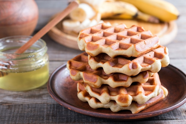 Homemade belgian waffles with with bananas and honey on a plate