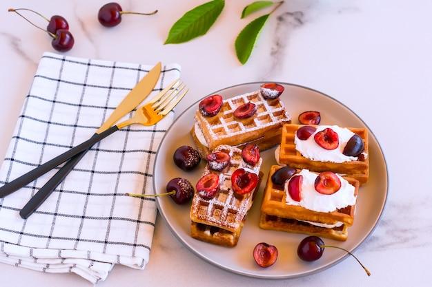 朝食にホイップクリームとチェリーを添えた自家製のベルギンワッフル。 Premium写真