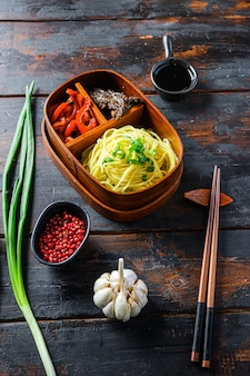 自家製弁当パックランチ、牛肉のグリル、麺と食材の側面図暗い木製のテーブル
