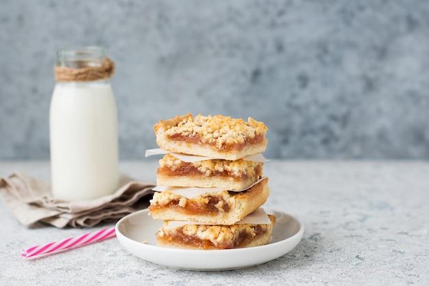 잼이 있는 홈메이드 베리 크럼블 바, 우유를 곁들인 홈메이드 쿠키, 선별적인 포커스