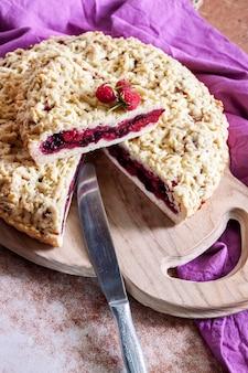 Домашний ягодный песочный пирог с крошкой на деревянной доске и фиолетовой ткани