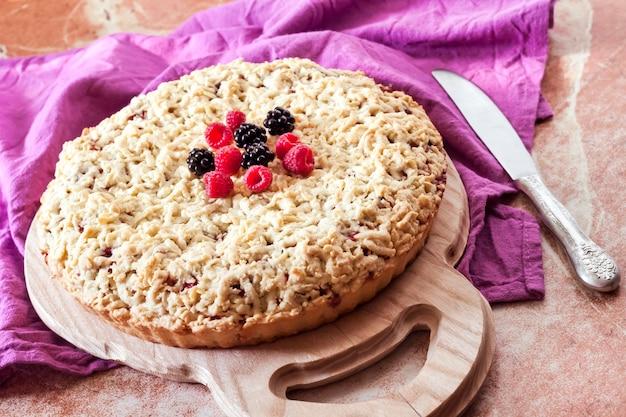 나무 판자와 보라색 천에 크럼블이 있는 홈메이드 베리 쇼트크러스트 파이