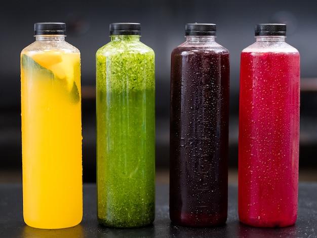 Homemade beverage assortment. bottles with yellow citrus, green cucumber lemonade, berries kompot, currant juice.