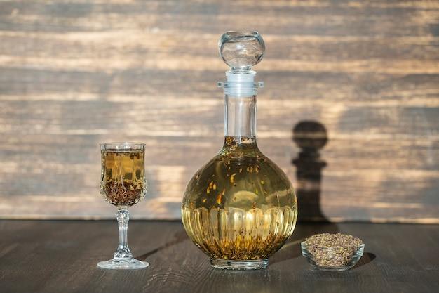 집에서 만든 자작나무 싹이 유리병에 든 팅크와 나무 탁자 배경에 있는 와인 크리스탈 유리가 닫혀 있습니다. 허브 알코올 음료 개념