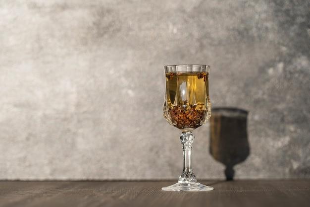 집에서 만든 자작나무 싹이 나무 테이블 배경에 있는 와인 크리스탈 유리에 팅크되어 있습니다. 허브 알코올 음료 개념