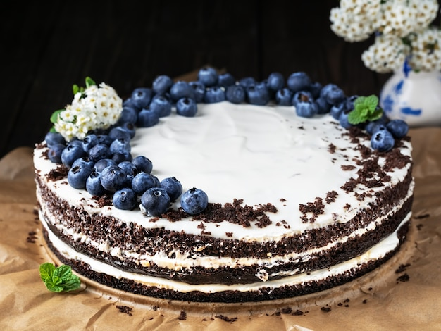 Homemade bird cherry cake with sour cream, decorated with blueberries and mint leaves on baking paper