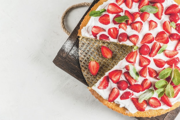 Homemade biscuit cake with whipped cream, fresh organic raw strawberries and mint.  white stone table.  top view