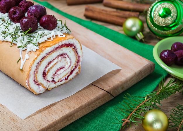 ヨーグルトクリームとクリスマスデコレーションの素朴なスタイルの自家製ビスケットチェリーロール