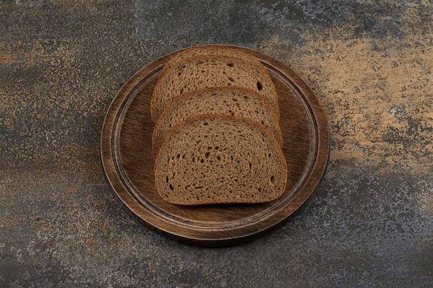 Homemade black bread slices on wooden board