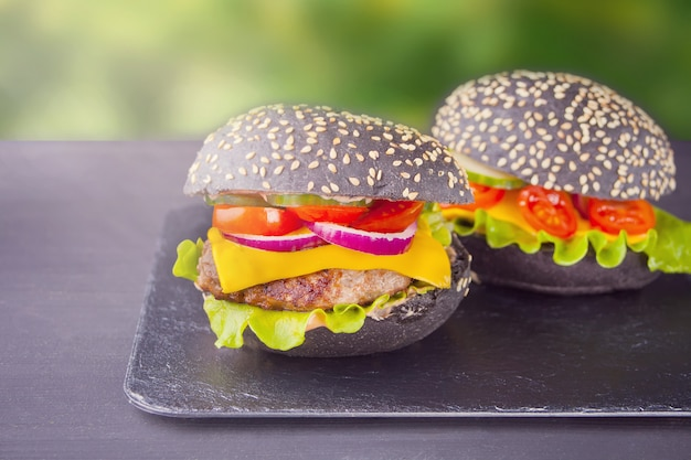 Homemade black burgers with cutlet and vegetables on the nature background
