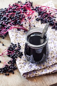 Homemade black elderberry syrup in glass jar and bunches of black elderberry in background