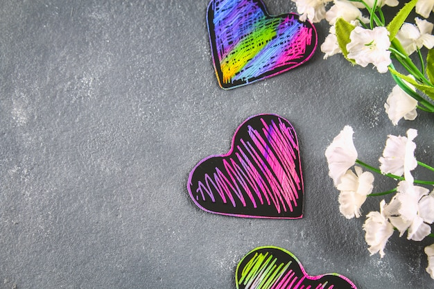 Homemade black violet pink hearts on a gray concrete background. the concept of valentine's day.