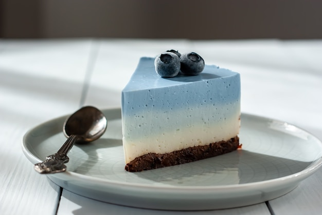 Homemade blue butterfly pea cheesecake with fresh berries on a light table