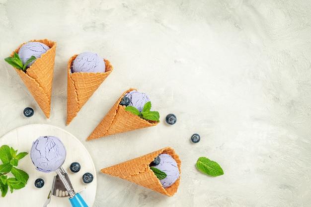 Домашнее черничное мороженое в вафельных рожках с листьями мяты. прямо над копией пространства