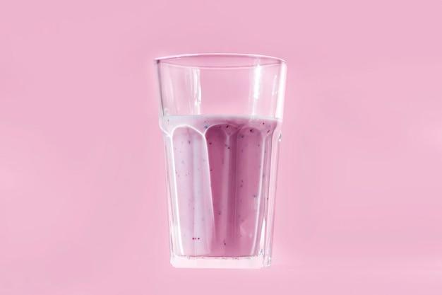 ピンクの背景に自家製ブルーベリーまたはスグリのスムージーフルーツまたはヨーグルト。適切な栄養と健康的な食事の概念。有機および菜食主義の飲み物。