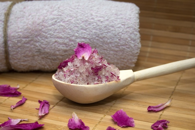 Homemade body scrub from sea salt and rose petals and peony pink towel on a straw mat