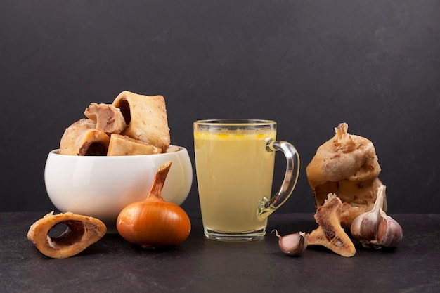Homemade boiled beef bone broth in transparent cup on dark  background with meat and vegetables. b