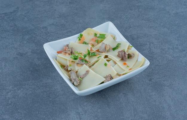 白い皿に乾いた肉の部分が入った自家製のゆで生地。