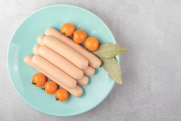 青い皿に自家製のボイル ソーセージとトマト。